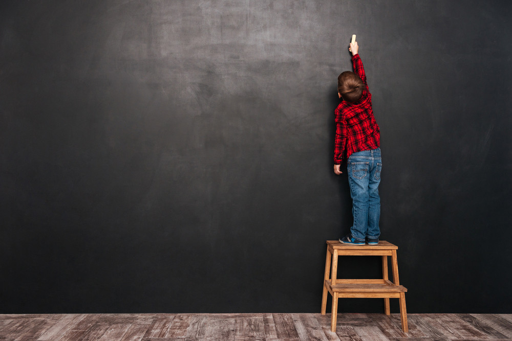 Picture of a little child standing on stool near blackboard and drawing on it.