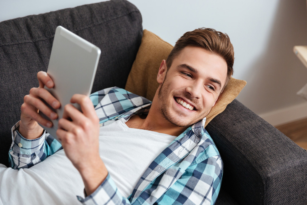Picture of a smiling bristle man dressed in shirt in a cage print lies on sofa in home and using tablet computer. Looking aside.
