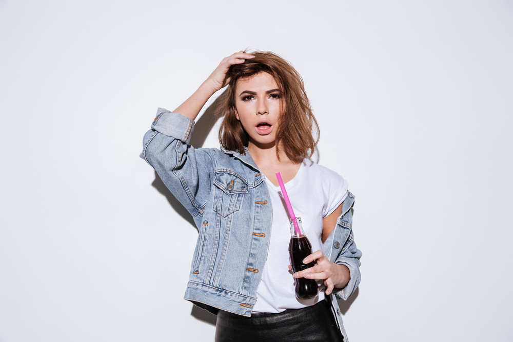 Picture of a young lady dressed in jeans jacket standing isolated over white background while drinking aerated sweet water.