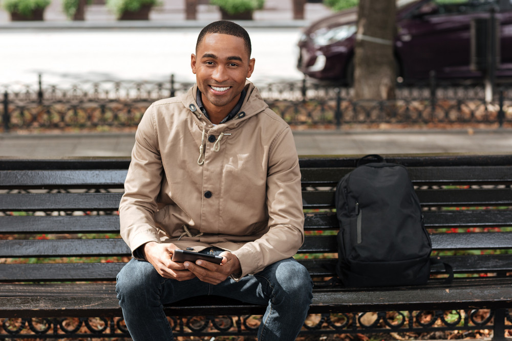 Picture of african happy man holding tablet while sitting on wooden bench near backpack and chatting. Look at camera.