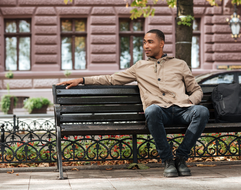 Picture Of African Happy Man Sitting On Wooden Bench Near Backpack