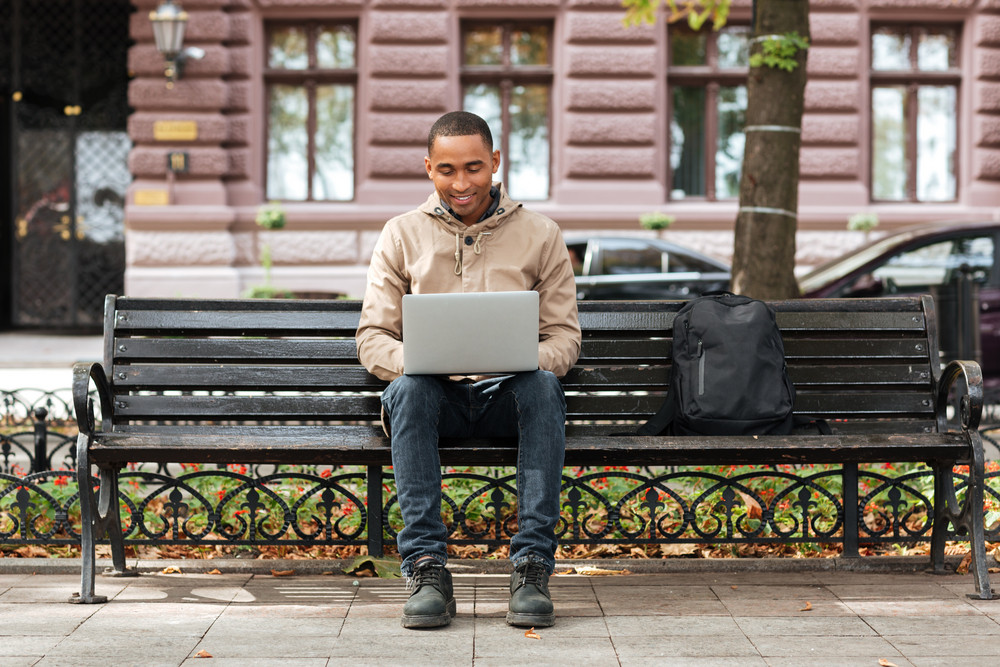 Picture of african man with laptop sitting on wooden bench near backpack and typing. Look at laptop.