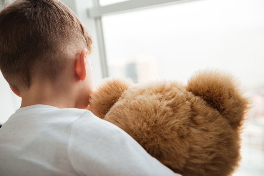 Picture of alone little sad boy standing with teddy bear near window and waiting for parents at home. Look at window.