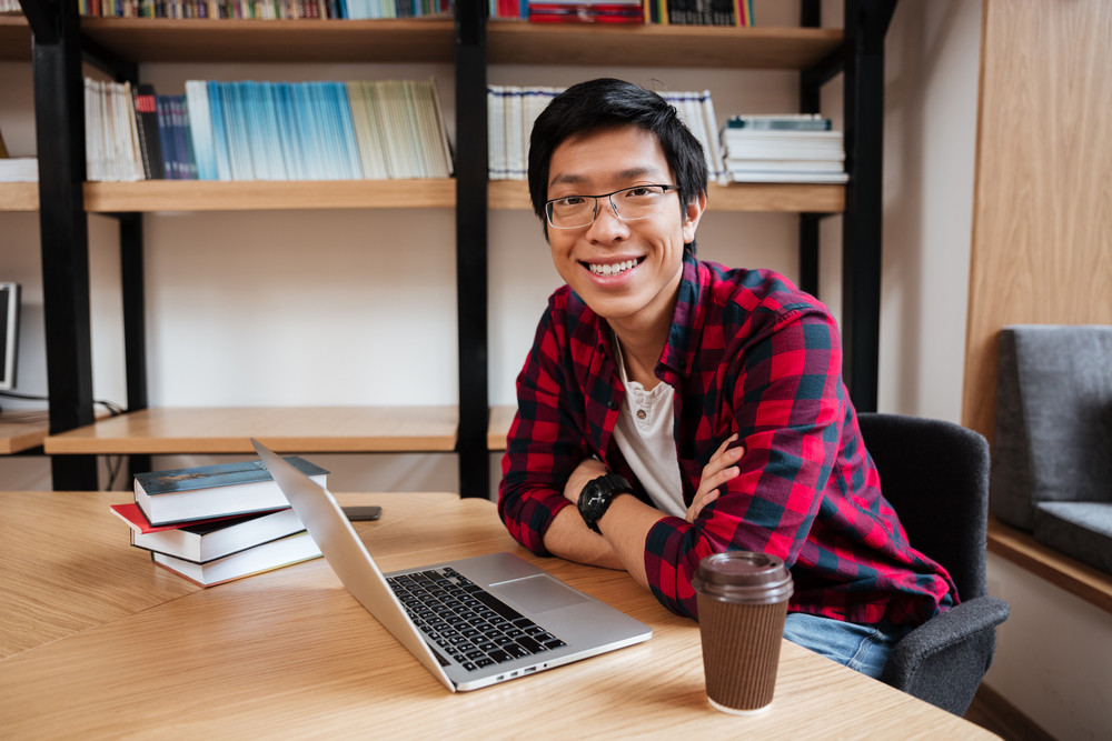 Picture of asian male dressed in shirt in a cage and wearing glasses using laptop at the library while drinking coffee. Looking at the camera.