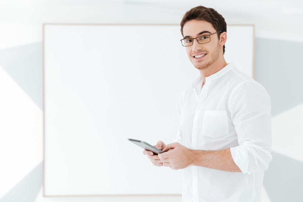 Picture of attractive man wearing eyeglasses and dressed in white shirt standing with tablet computer near big board. Look at camera.