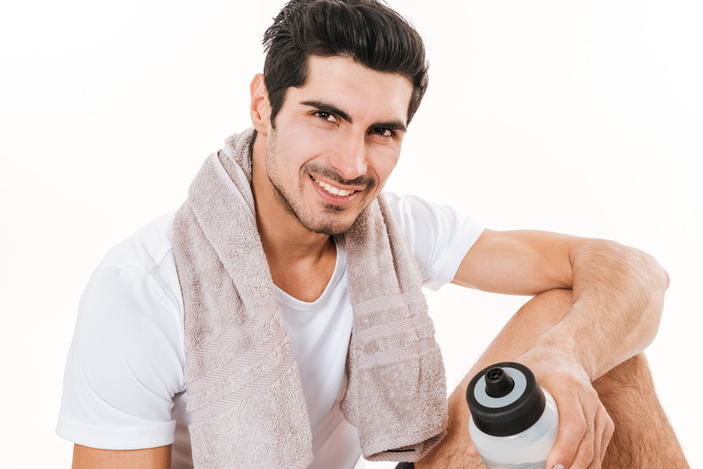 Picture of attractive sportsman with towel in gym sitting on floor over white background. Look at camera and smile while holding bottle of water.