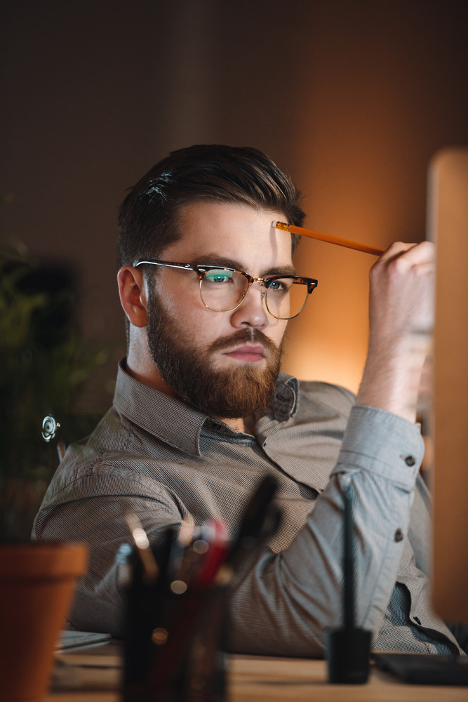 Picture of attractive web designer dressed in shirt and wearing eyeglasses working late at night and looking at computer. Holding pencil.