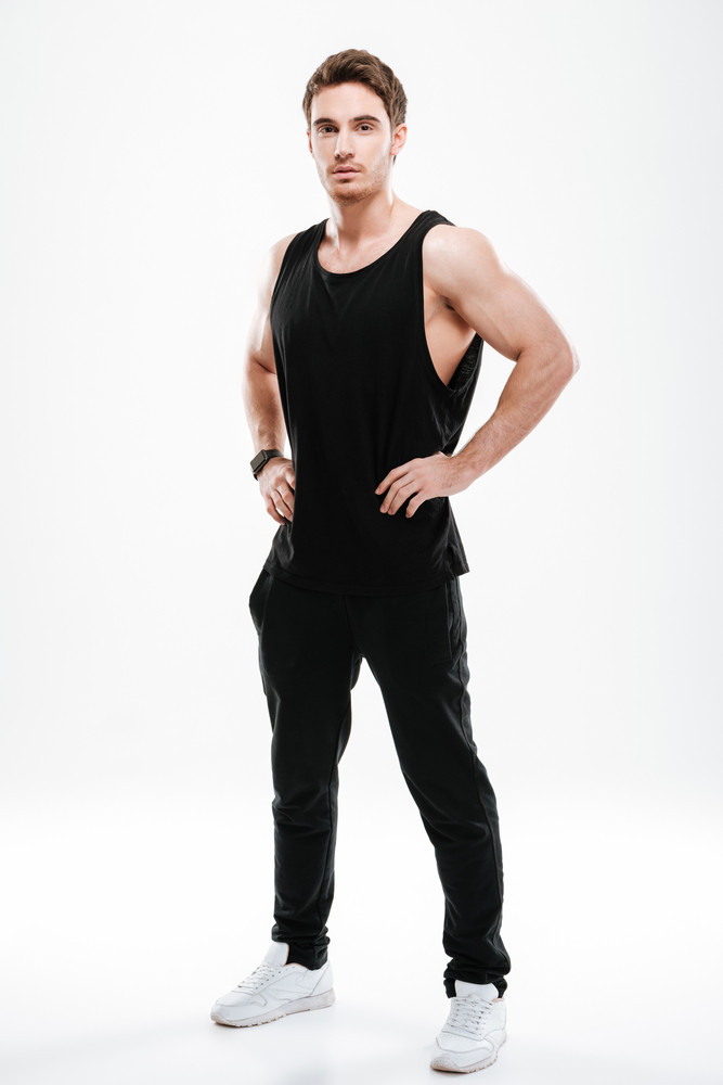 Picture of attractive young man dressed in black t-shirt standing over white background and looking to camera.