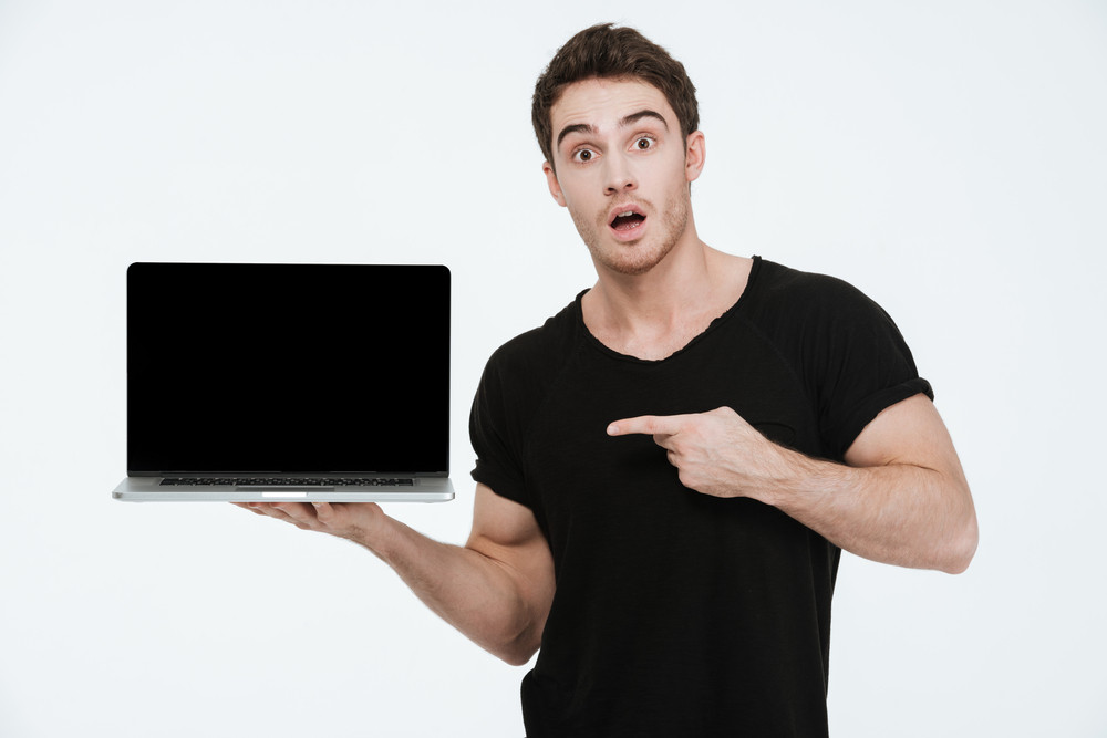 Picture of attractive young man dressed in black t-shirt standing over white background showing display of his laptop computer and pointing.