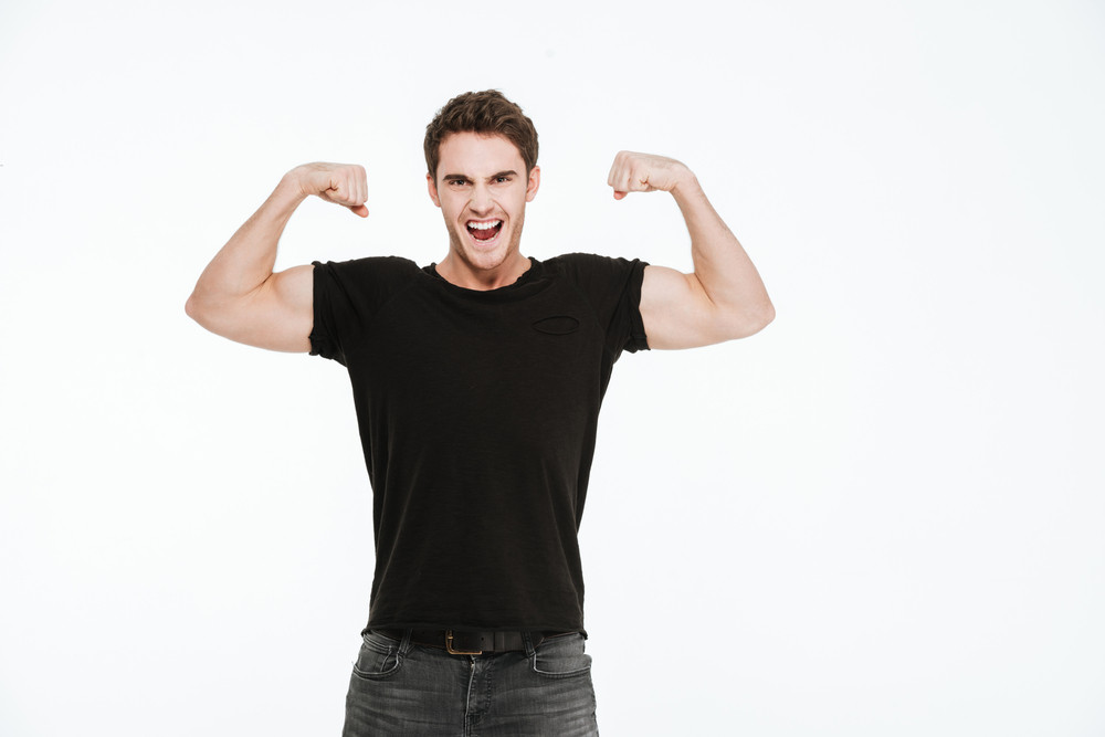 Picture of attractive young man dressed in black t-shirt standing over white background showing his biceps.