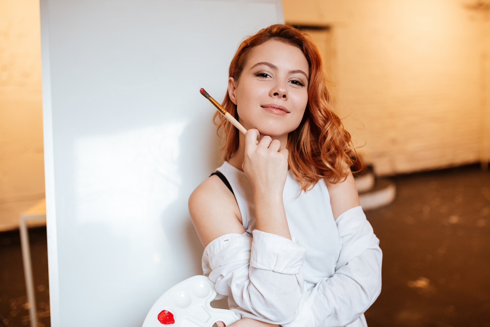 Picture of beautiful young woman painter with red hair standing over blank canvas in artist workshop. Look at camera while holding palette and paintbrush.
