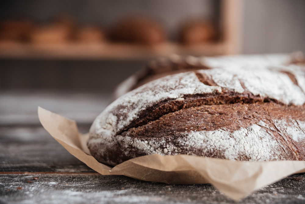 Picture of bread with flour on dark wooden table at bakery