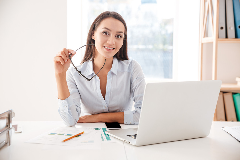 Picture of businesswoman dressed in white shirt and holding glasses sitting in her office and using laptop. Looking at camera.