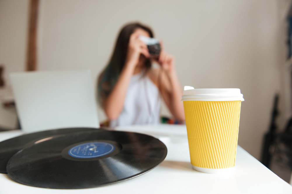 Picture of casual lady working on a laptop sitting on the chair in the house while using camera. Focus on table with vinyl record and coffee.