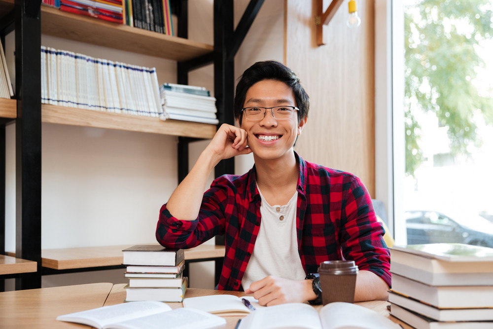 Picture of cheerful asian man dressed in shirt in a cage and wearing glasses sitting with books at the library. Looking at camera.