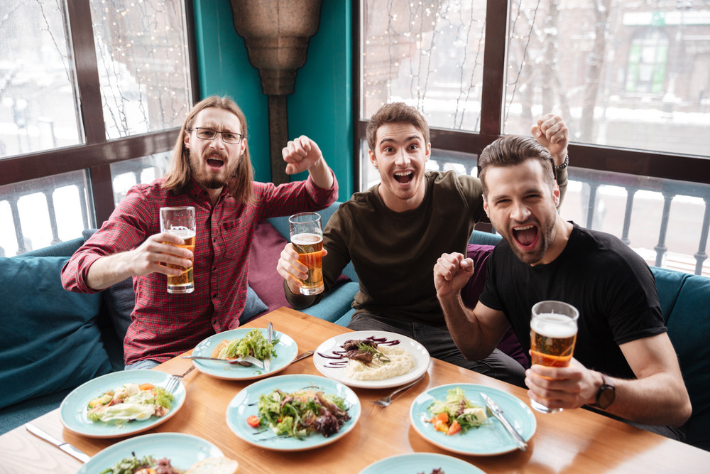 Picture of cheerful men friends sitting in cafe while eating and drinking beer.