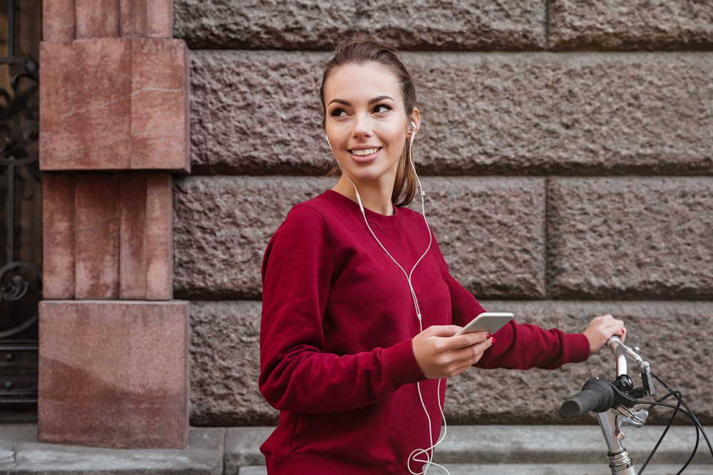 Picture of cheerful woman dressed in sweater walking with her bicycle in the city while standing near wall and listen to music by her phone. Look aside