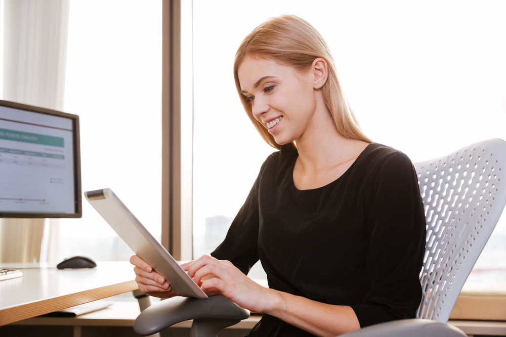 Picture of cheerful woman worker sitting in office while using tablet computer. Look at tablet.