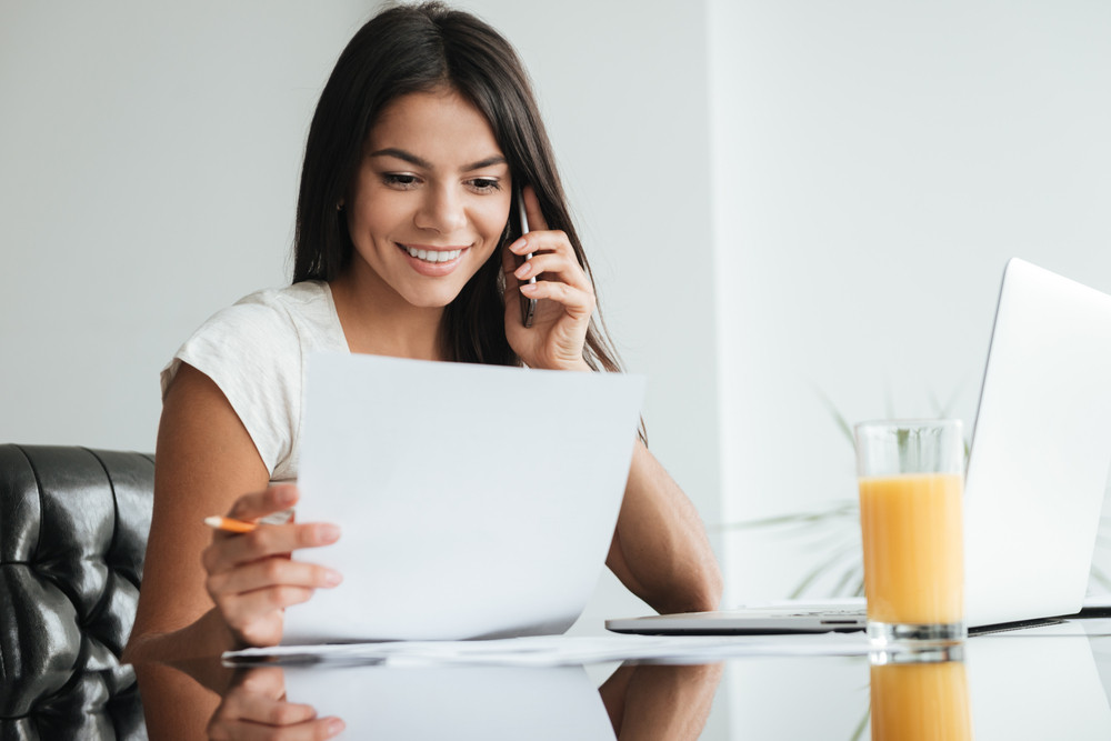 Picture of cheerful young lady using laptop and analyzing home finances with documents. Look at documents while talking by cellphone.
