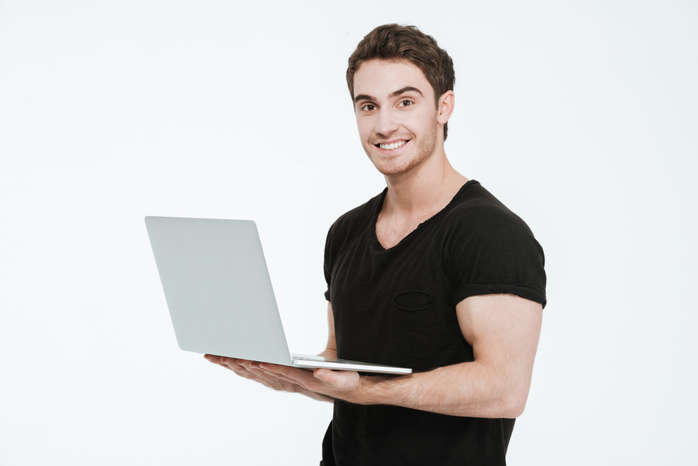 Picture of cheerful young man dressed in black t-shirt standing over white background holding laptop computer and look at camera.