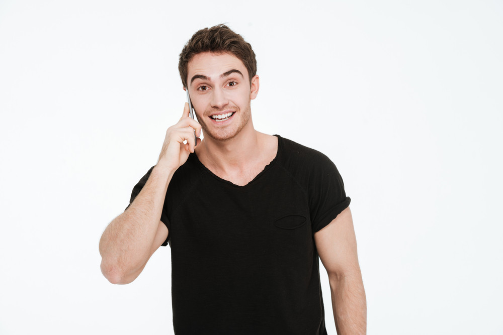 Picture of cheerful young man dressed in black t-shirt standing over white background talking by his phone.