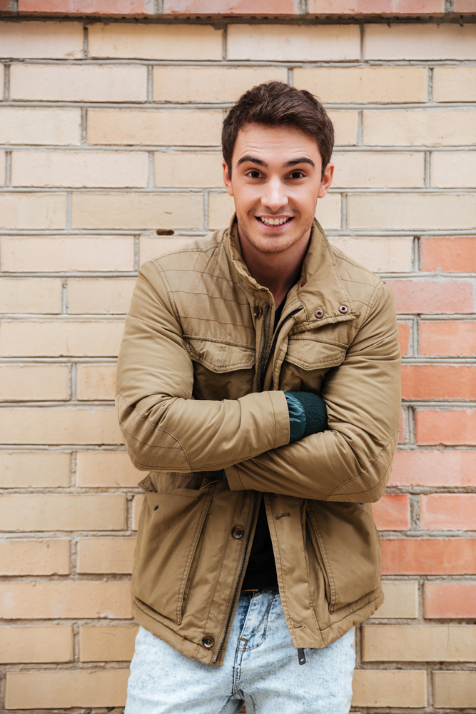 Picture of cheerful young man walking on the street and looking at camera.
