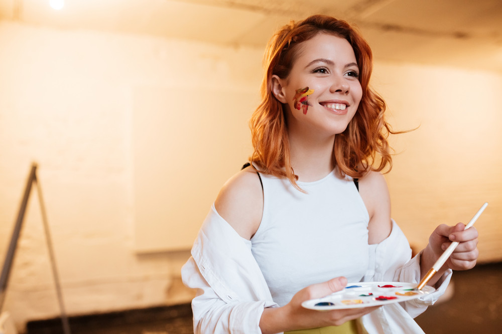 Picture of cheerful young redhead woman painter with oil paints on face in artist workshop. Look aside while holding palette.