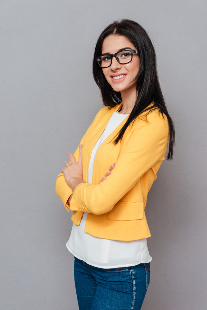 Picture of cheerful young woman wearing eyeglasses and dressed in yellow jacket posing over grey background with arms crossed. Look at camera.