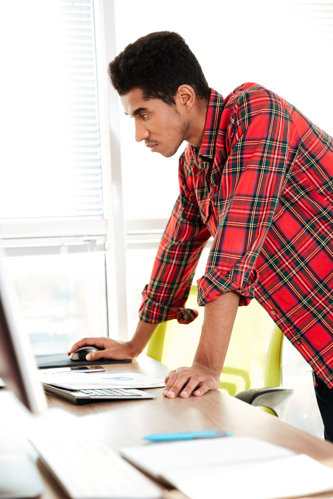 Picture of concentrated african guy dressed in shirt in a cage print standing in room while looking at computer.