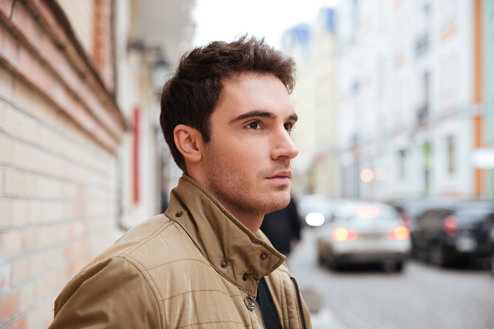 Picture of concentrated young man walking on the street and looking aside.