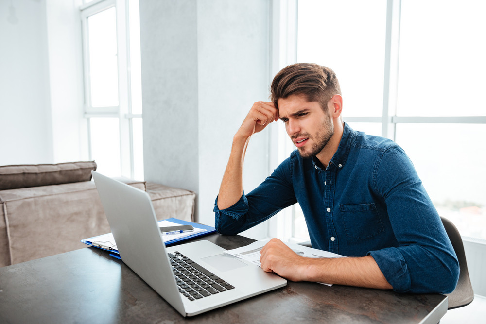 Picture of confused young man sitting near laptop and holding head with his hand. Looking at laptop.
