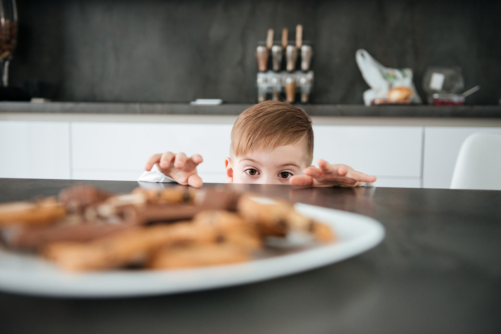 Picture of cute boy standing in kitchen while tries to take cookies and chocolate.
