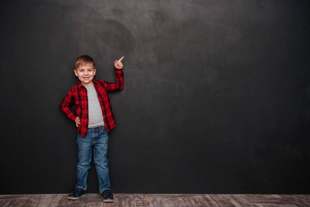 Picture of cute little boy standing over chalkboard and pointing up. Looking at camera.