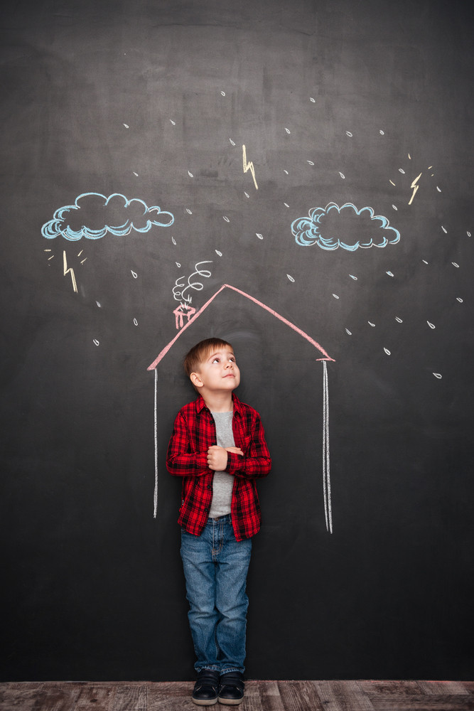 Picture of cute little kid standing in house on the chalkboard with drawings of a rain. Looking up to drawings.