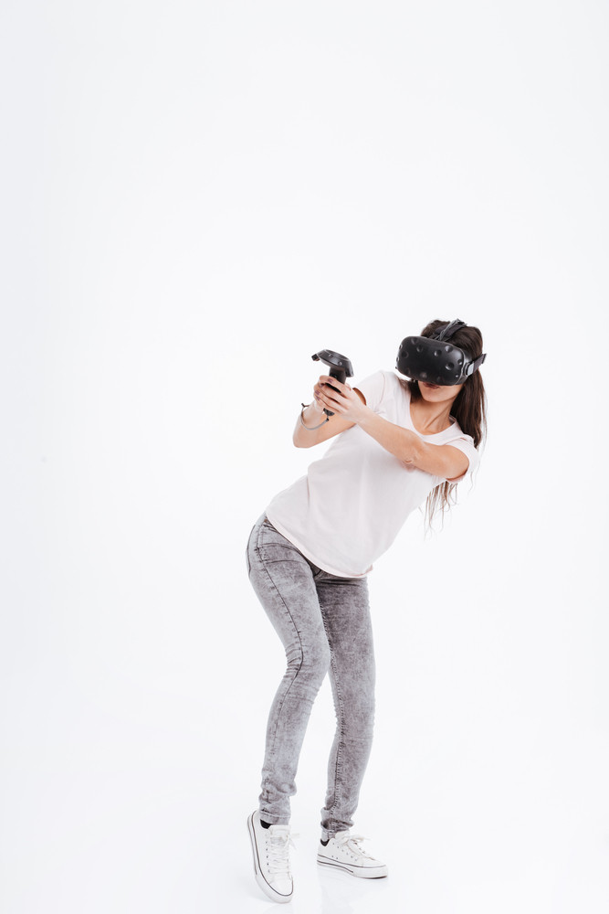 Picture of emotional lady wearing virtual reality device while holding joysticks over white background.
