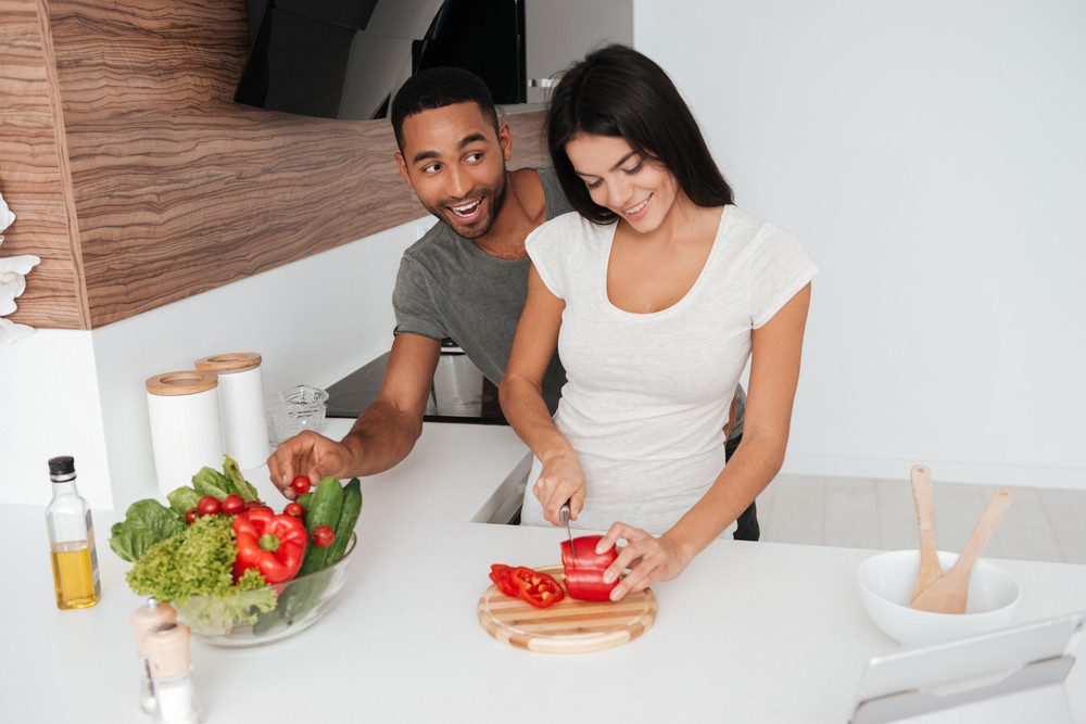 Picture of funny loving couple in the kitchen cooking. Man takes away the products.