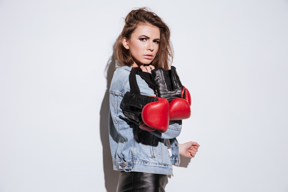Picture of gorgeous lady boxer dressed in jeans jacket and gloves isolated over white background