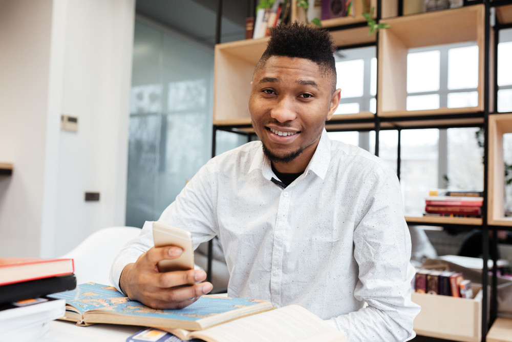 Picture of handsome african student in library learning education material with book while chatting by his phone. Looking at camera.