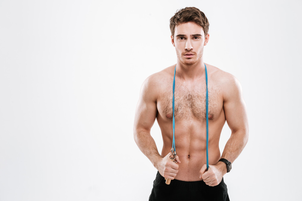 Picture of handsome athlete standing with jumping rope over white background.