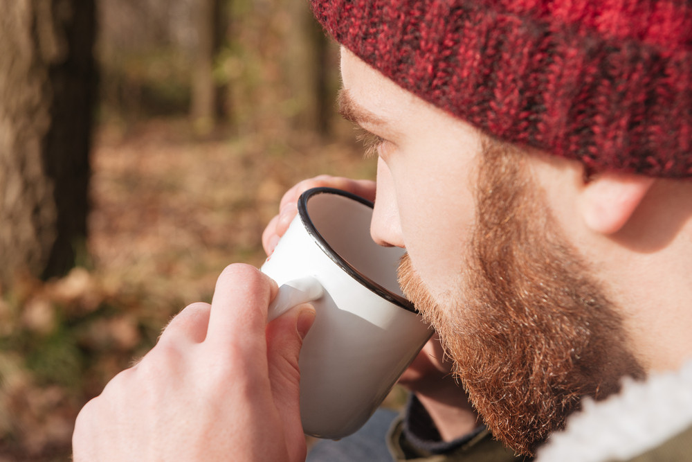 Picture of handsome bearded man wearing hat holding cup of tea in hands standing in the forest and drinking.
