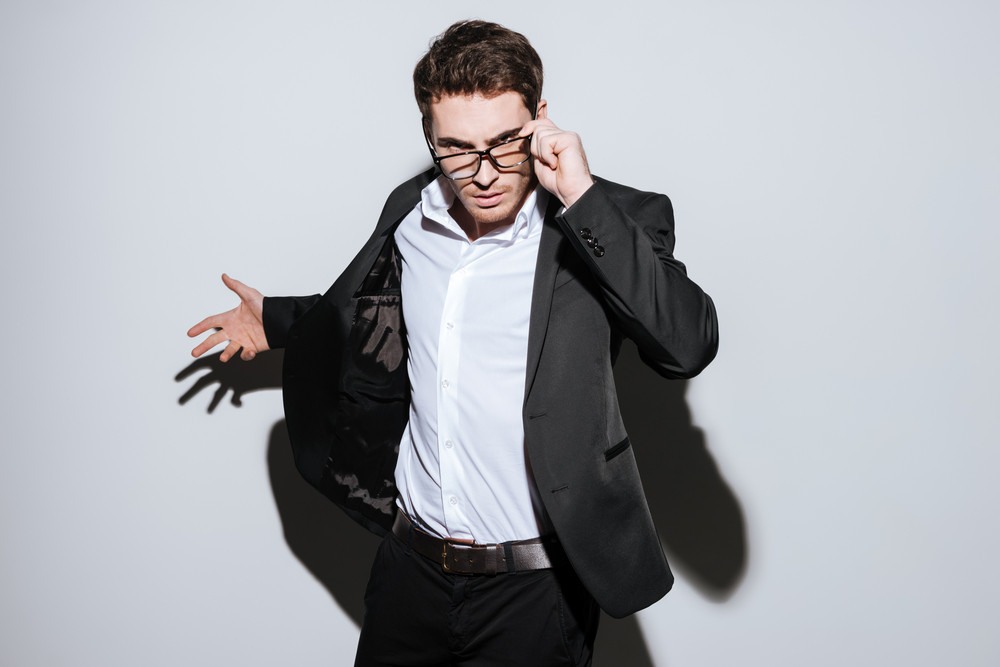 Picture of handsome businessman wearing glasses standing at studio and look at camera. Isolated over white background