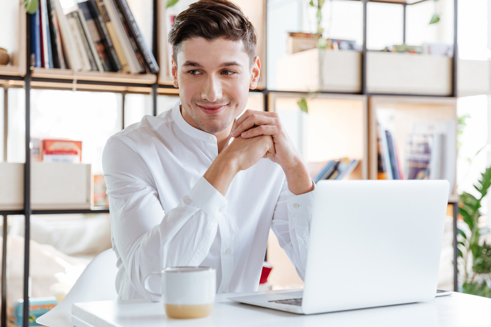 Picture of handsome man dressed in white shirt drinking coffee and using laptop computer. Coworking. Looking at camera.