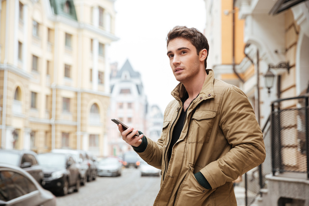 Picture of handsome man walking on street and chatting by his phone outdoors. Look aside.