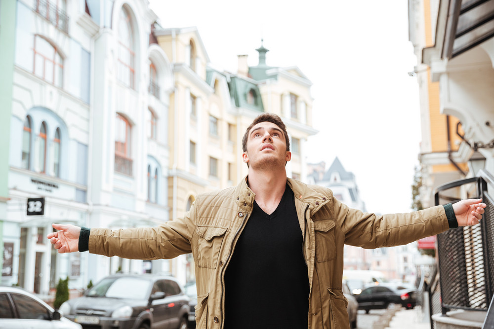 Picture of handsome young man walking on the street and looking up to sky.
