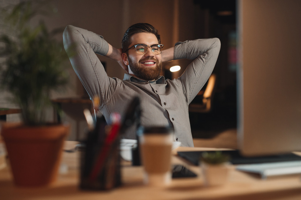 Picture of happy bearded designer dressed in shirt working late at night with computer and stretching.