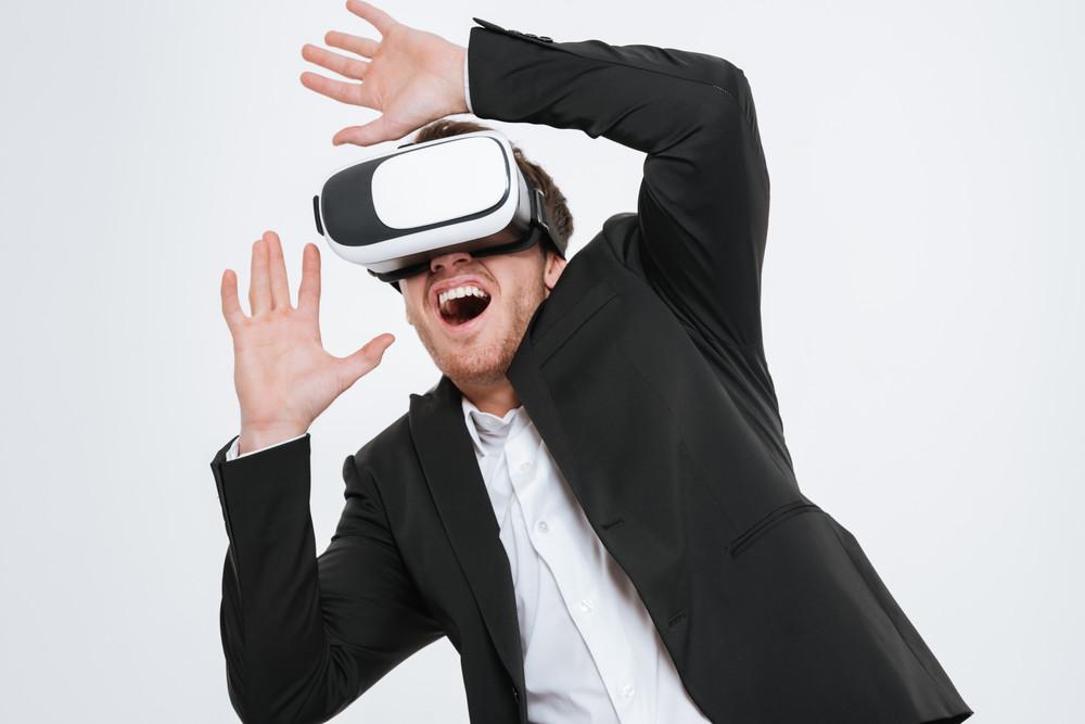 Picture of happy businessman standing at studio wearing 3d glasses virtual reality. Isolated over white background.
