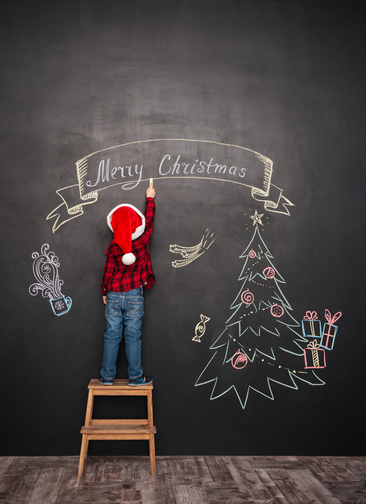 Picture of happy child wearing hat standing on stool near Christmas tree while drawing on blackboard.