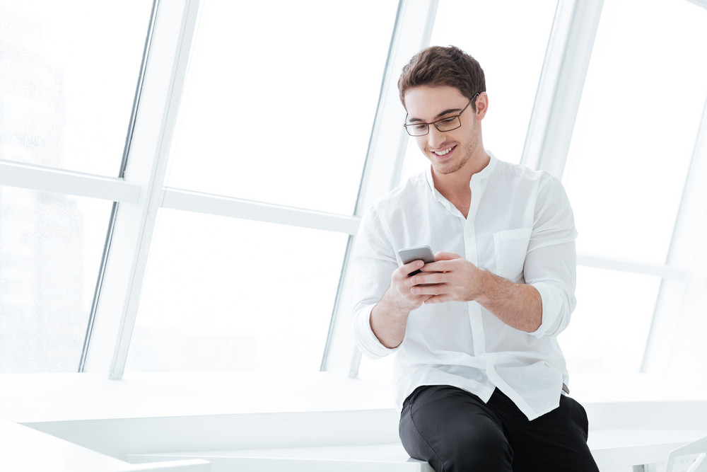 Picture of happy man wearing eyeglasses and dressed in white shirt sitting on white table while using phone. Looking at phone.