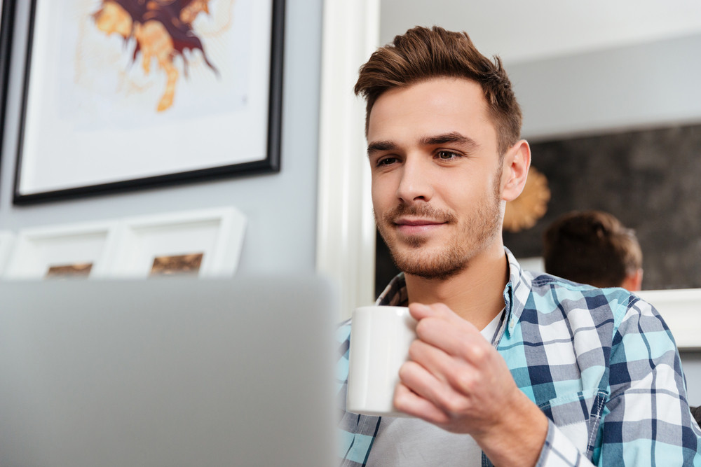 Picture of happy young man dressed in shirt in a cage print sitting on sofa in home and using laptop computer. Looking at laptop while drinking tea.