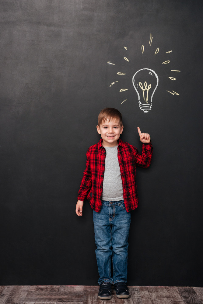 Picture of little boy pointing up and having an idea over chalkboard background with drawings. Looking at camera.